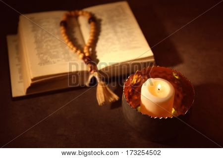 Bible and burning candle on table
