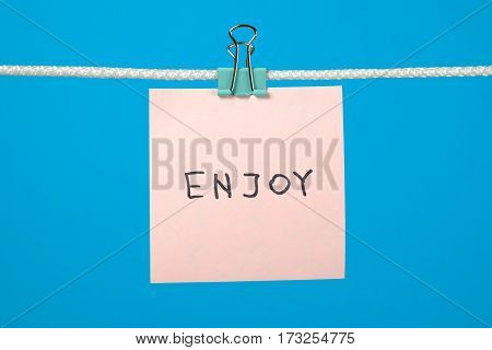 Pink Paper Note On Clothesline With Text Enjoy