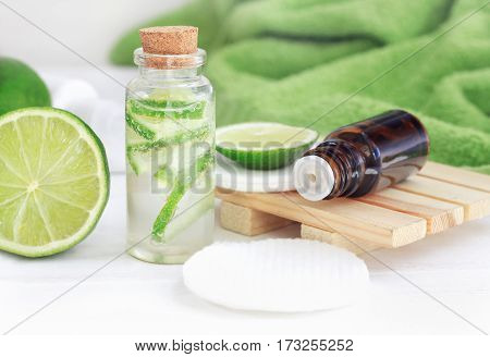 Lime essential oil and skincare tonic with bubbles in glass bottle, fresh fruit. Green and white colors for home spa.