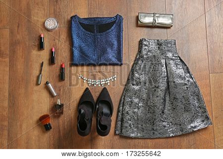 Flat lay set of female clothes and accessories on wooden background