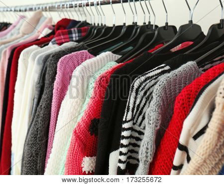 Clothes on hangers in modern shop, closeup