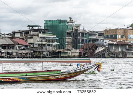 Bangkok Thailand 03.10.2015 Long tail boat on river Bangkok poor houses ruins chao Phraya