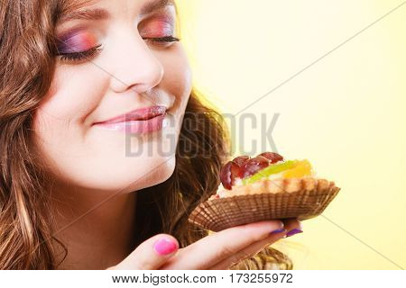 Bakery sweet food indulging and people concept. Cute attractive woman closed eyes holds cake cupcake in hand smelling yellow background