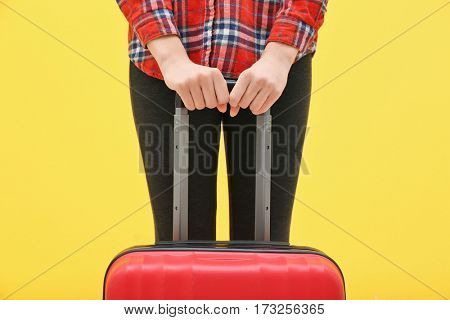 Young tourist with suitcase on yellow background