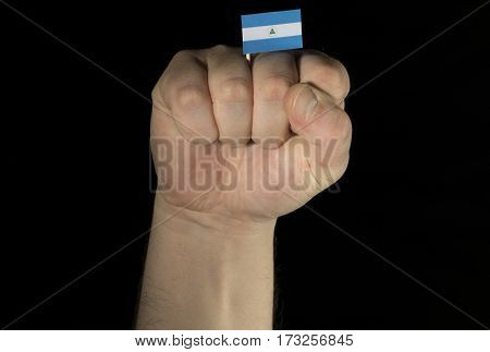 Man Hand Fist With Nicaraguan Flag Isolated On Black Background