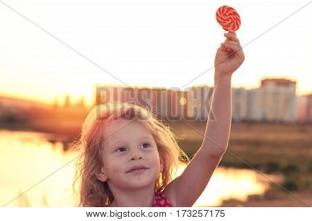Happy little girl with Lollipop outdoors at sunset.