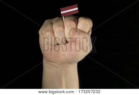 Man Hand Fist With Latvian Flag Isolated On Black Background