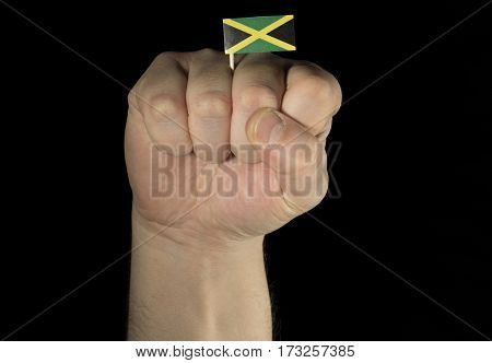 Man Hand Fist With Jamaican Flag Isolated On Black Background