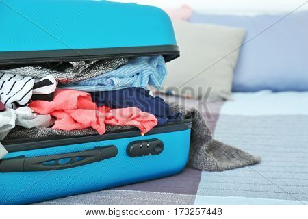 Open packed travel suitcase at home, closeup