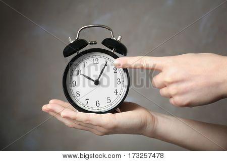 Woman holding vintage alarm clock on color background