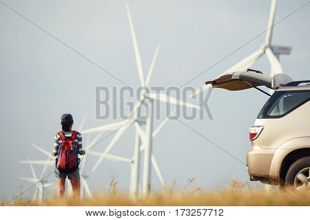 Hipter woman backpacker a lone travel and wind turbines on background