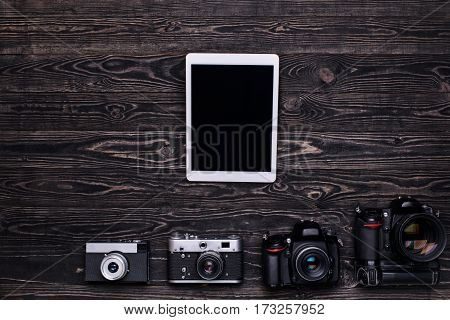 Retro camera,modern DSLR camera and tablet computer on dark wooden table