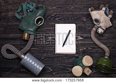 Two old gas mask,respirator and notepad with pen on dark wooden table.Top view