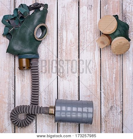 Old gas mask and respirator on light wooden background.Top view