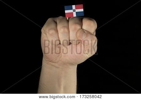 Man Hand Fist With Dominican Republic Flag Isolated On Black Background