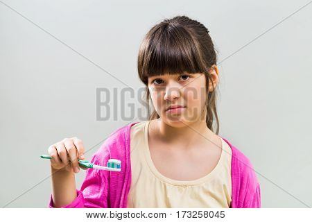 Photo of sad little girl with toothbrush.