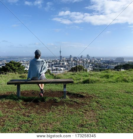 Woman on bench looking at city skyline of Auckland New Zealand