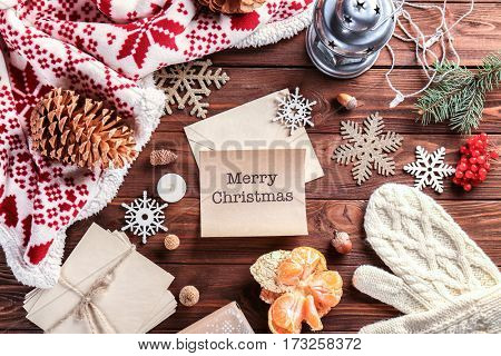 Christmas decorations and wish card on wooden background