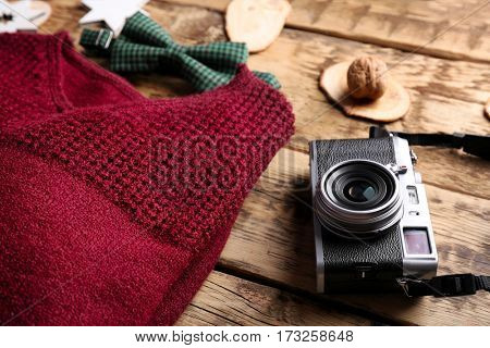 Retro camera and knitted pullover on wooden background