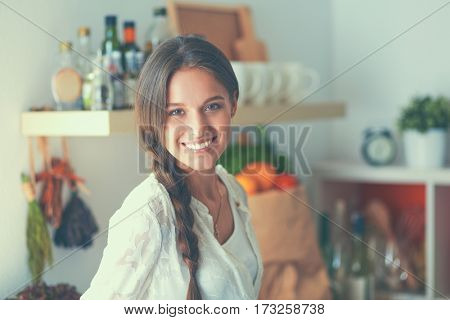 Young woman standing near desk in the kitchen