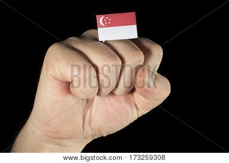 Man Hand Fist With Singaporean Flag Isolated On Black Background