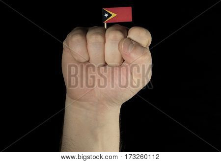 Man Hand Fist With East Timor Flag Isolated On Black Background