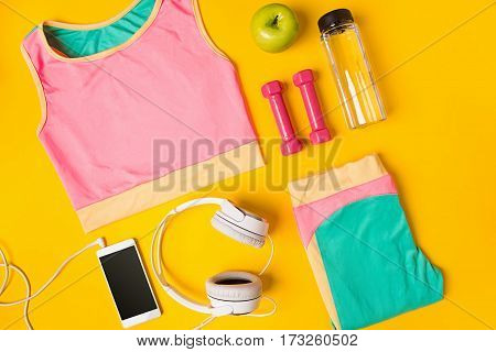 Sport equipment and clothes with mobile phone on yellow background. Still life. Top view