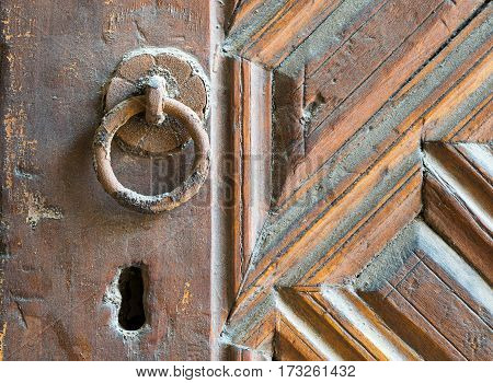 Closeup of rusted ring door knob over an aged decorated wooden door Old Cairo Egypt