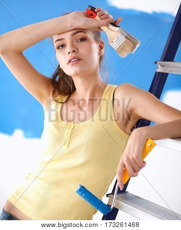 Beautiful young woman doing wall painting, standing near ladder