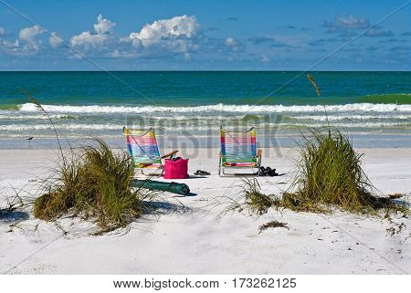 Two Colorful Beach Chairs and Tote Bag on the Florida Coast