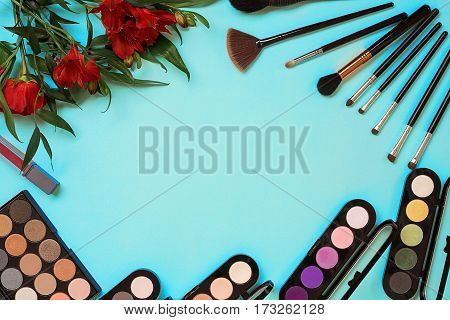 Top view on set of cosmetics for professional make-up on blue background. Still life. Copy space