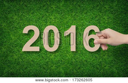 Year 2016 - Hand holding paper alphabet number on green grass background.
