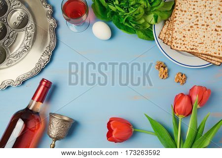 Passover holiday concept seder plate matzoh tulip flowers and wine bottle on wooden background. Top view from above