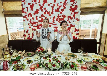 stylish bride and happy groom in the restaurant centerpiece reception having fun and kissing