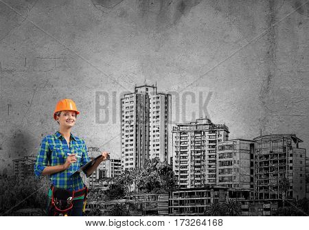 Engineer woman with folder and sketches of construction project on wall