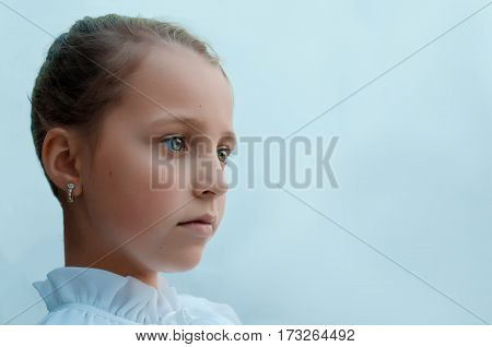 Girl sad and specifically looks into the distance on a uniform blue background