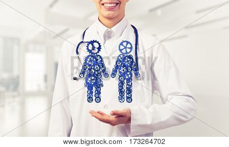 Figures of man and woman made of gears and cogwheels in doctor palm. Mixed media