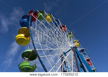 Ferris wheel with colored cabins on the blue sky background Sunny day clouds ride fair fun