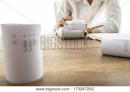 Business accountant or financial adviser making calculations using adding machine.