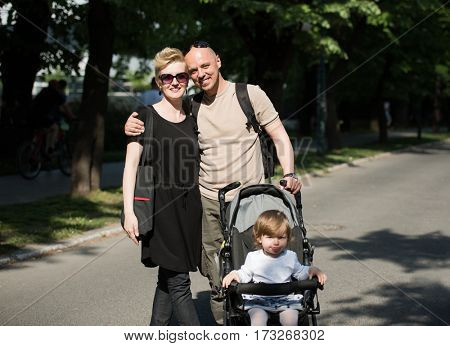 love, parenthood, family, season and people concept  Portrait of a young smiling couple with baby pram in summer park