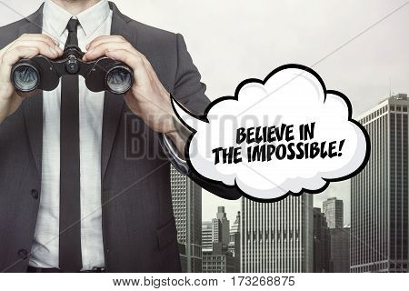 Believe in the impossible text on  blackboard with businessman and key