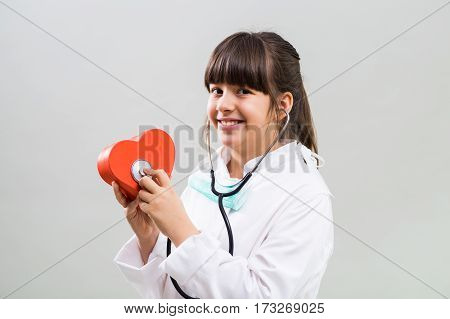Little cardiologist holding heart shape and stethoscope.