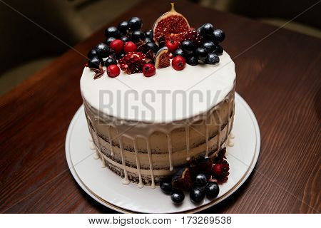 Birthday cake decorated with fresh fruit on a white plate on a wooden table. A wedding cake.