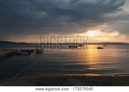 Fishing boats anchored in the bay at sunset with orange sun reflecting in the water and gathering storm clouds in the background