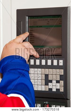 Automated workplace, engineer's hand on the working computer panel of industrial CNC machine