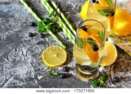 Traditional summer drink with lemon blueberry and mint on a concrete background