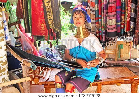 MAE HONG SON, THAILAND - JUNE 17, 2014: Unidentified Padaung (Karen) tribe woman weave on traditional device near Mae Hong Son, Thailand, Chiang rai Karen Long Neck hill tribe village. Padaung women wear brass rings on the neck since the age of 5 years