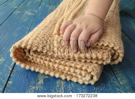 warm soft blanket and a child's hand a wooden surface