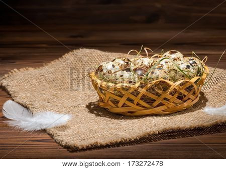 Quail Eggs With Straw And Feathers In Basket On Sackcloth, Rural Style, Close Up