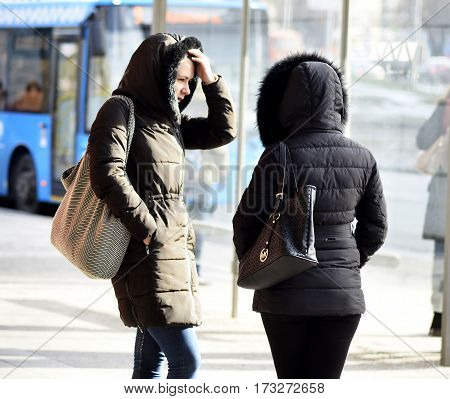Russia. Moscow. 02-25-2017 12:26 two women talking in the afternoon at a bus stop